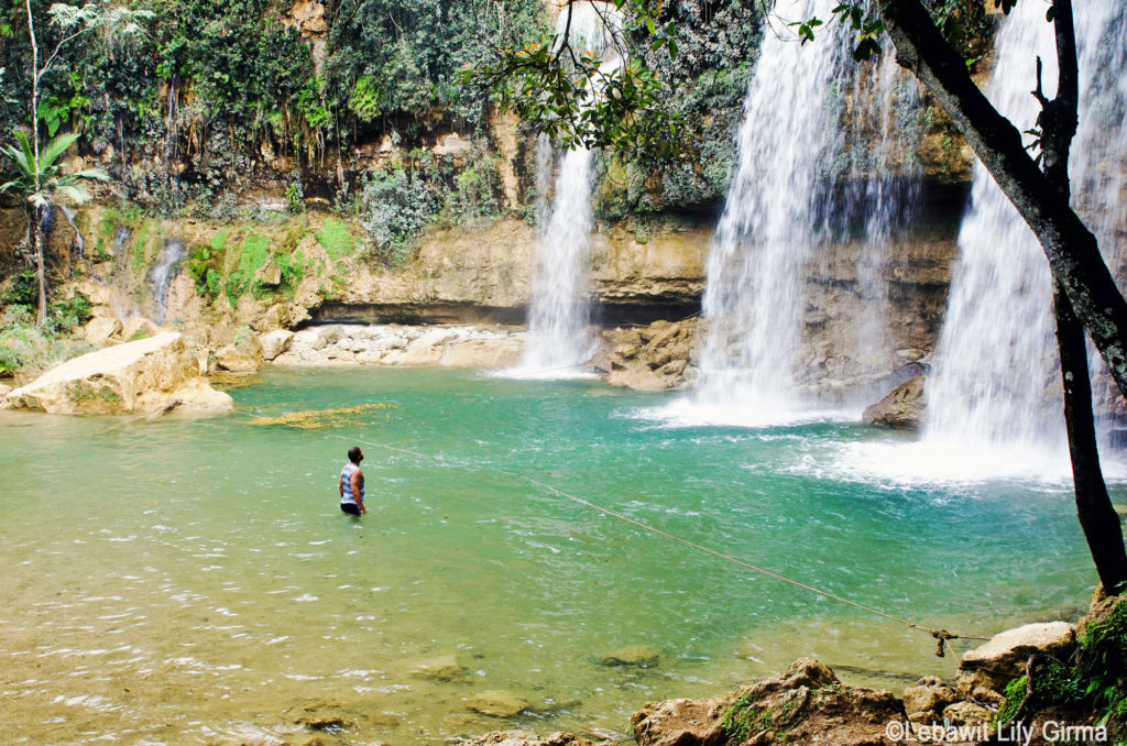 Man standing in front of Salto Alto waterfall, Dominican Republic.