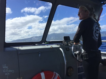 Julia, our safety diver, steering the boat to the ocean shelf.