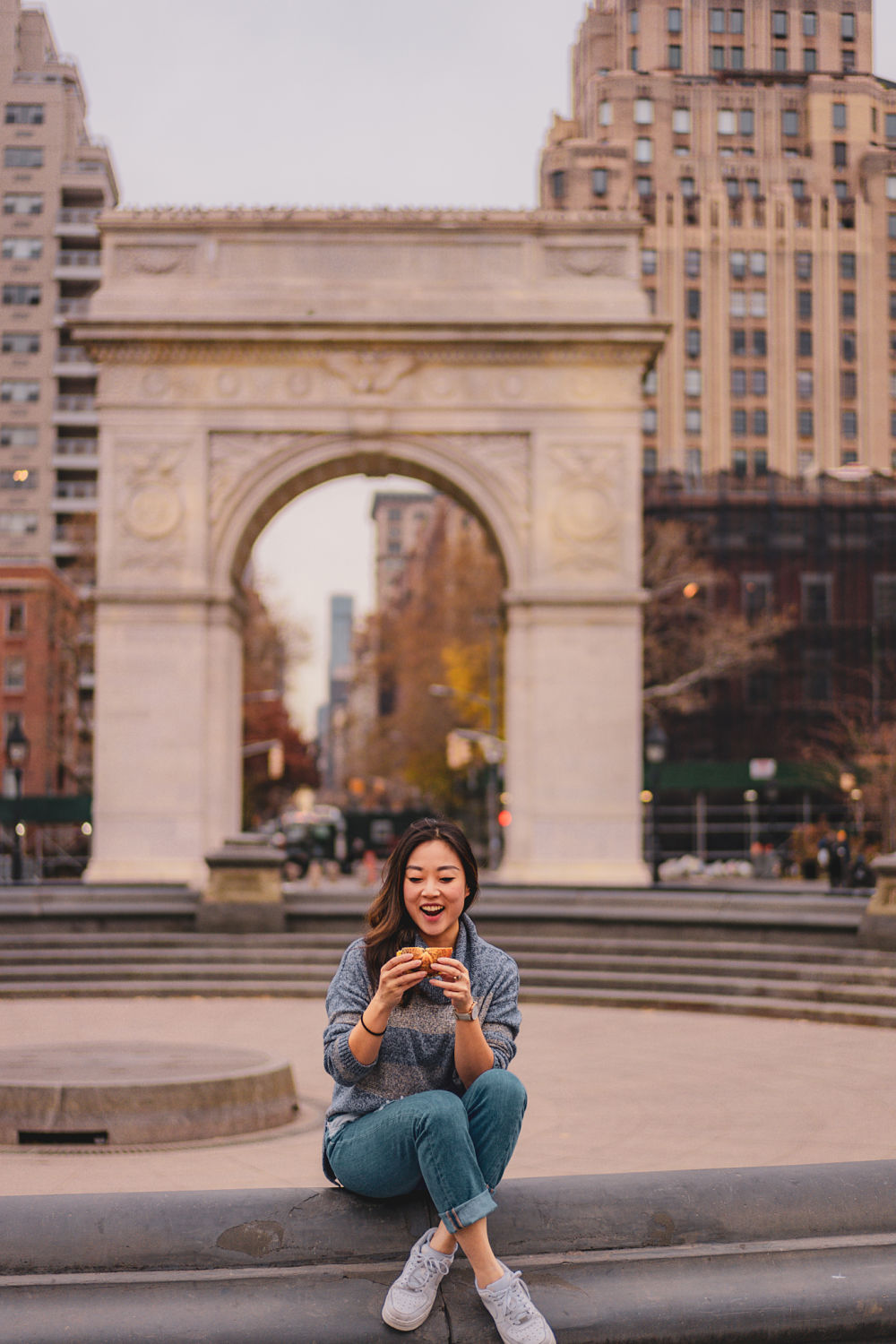 A girl eating a bagel in Washington Square Park in Manhattan New York City