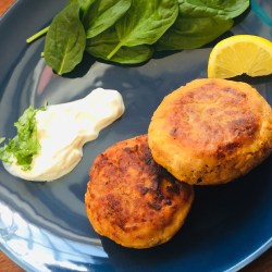 Salmon, sweet potato coriander fish cakes on a bowl plate with spinach and crème fraiche