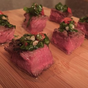 Filet steak cubes sitting on a wooden board topped with chimichurri sauce