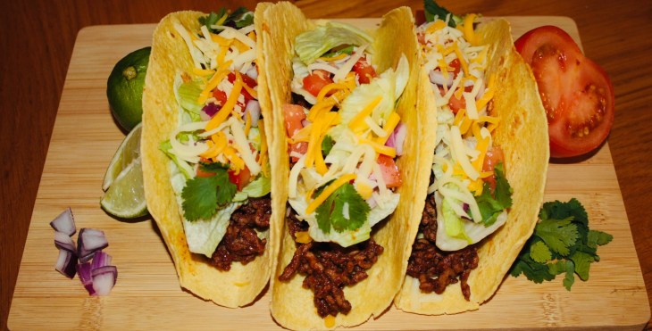 Three yummy beef tacos with loads of toppings served on a wooden board.
