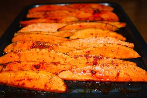 Sweet potato wedges with spicy marinade all over. Sitting on the oven tray ready to go in