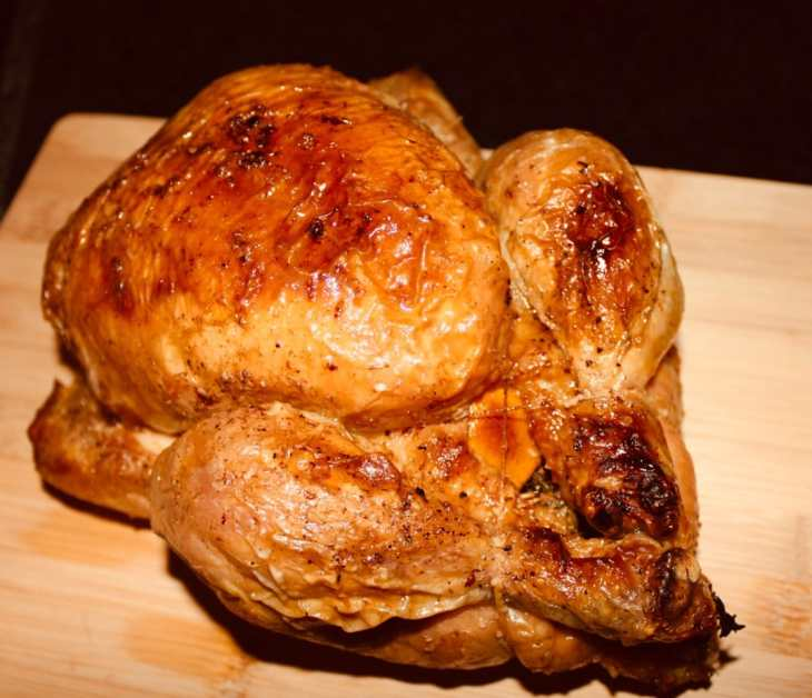 A full crispy golden lemon and thyme roast chicken resting on a wooden board.