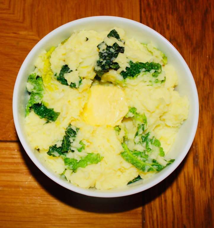 Traditional Irish creamy colcannon serve in a side bowl with a knob of melting butter on top.