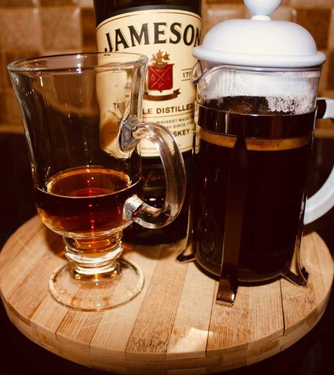 Freshly brewed coffee with Jameson whiskey in a heat proof glass.