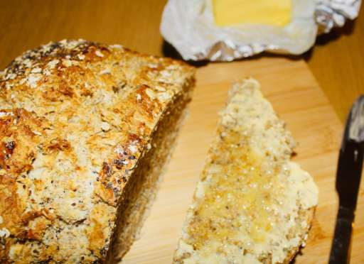 Warm soda bread served on a wooden tray with lots of butter.