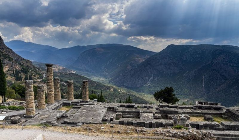 ancient ruins of delphi and the sun peaking through the clouds - Winter Holidays in Greece: the best travel ideas