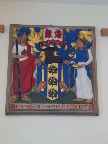 Shield at the entrance to the Royal National Throat, Nose and Ear Hospital which houses the library – wording reads 'Audient Surdi, Mutique Loquentur' which roughly translates as 'the deaf hear, the mute speak'.
