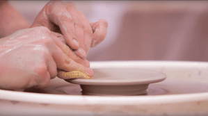 Hands sculpting soft clay on a pottery wheel