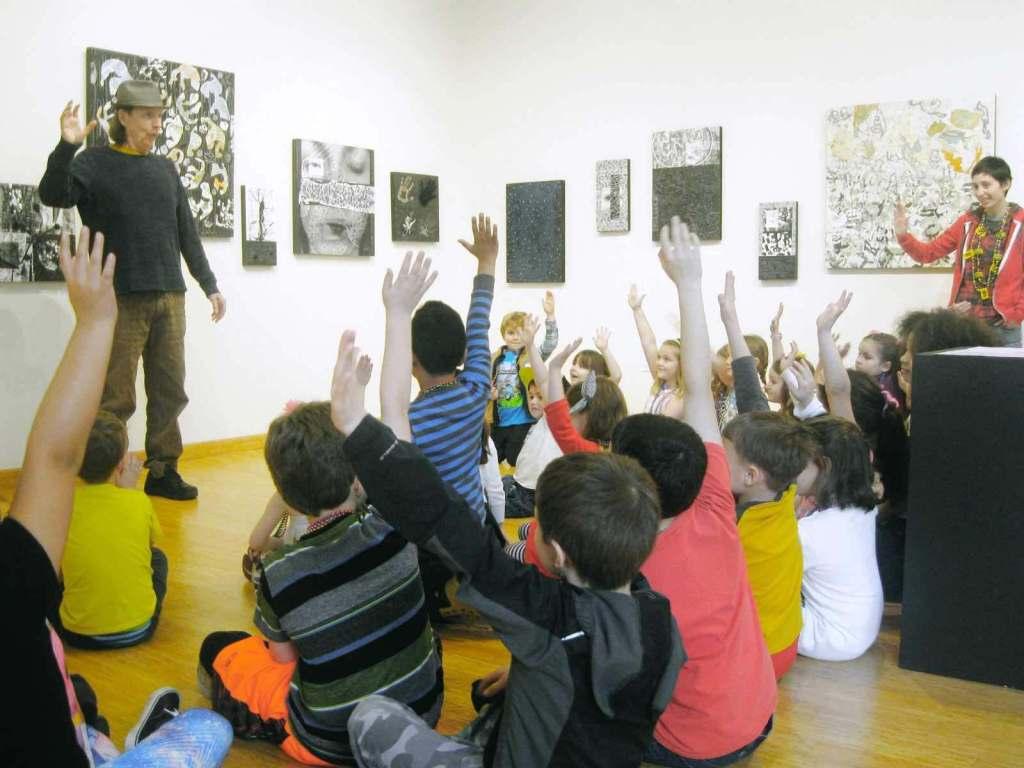 Kids raising hands in gallery