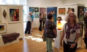 Colorful gallery reception with people looking at art