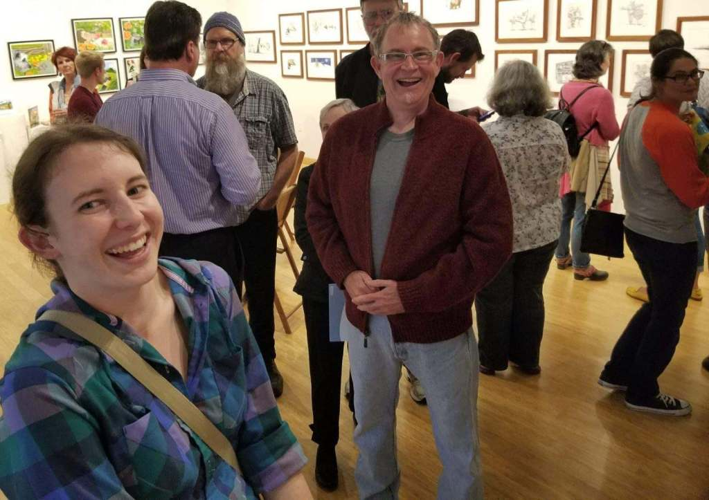 Bustling gallery reception with two people looking towards the viewer