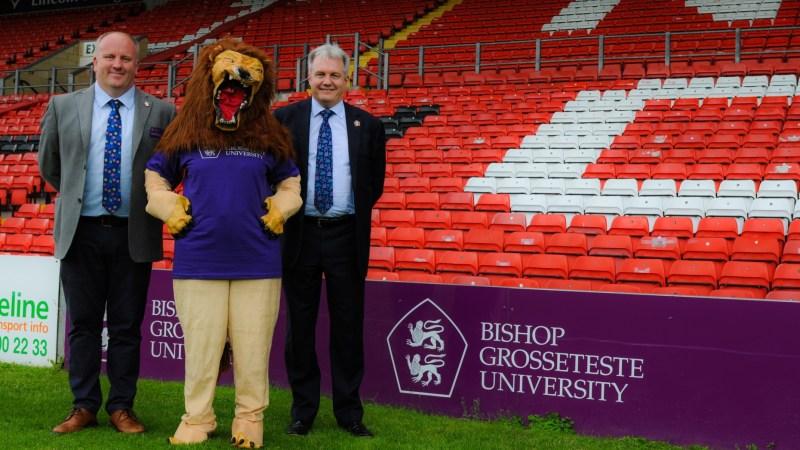 Dr Graham Basten, Head of Social Sciences at BGU, with the Reverend Canon Professor Peter Neil, Vice Chancellor of BGU, and a BGU lion mascot pictured at Sincil Bank stadium. Photo: Emily Bennett / BGU