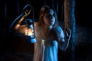 Closeup portrait of scared woman lost in forest lighting up the way with lantern