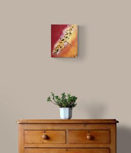 Tableau abstrait rouge orange et jaune accroché au mur