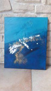 Tableau abstrait bleu doré et blanc posé sur un mur en pierre - Faro