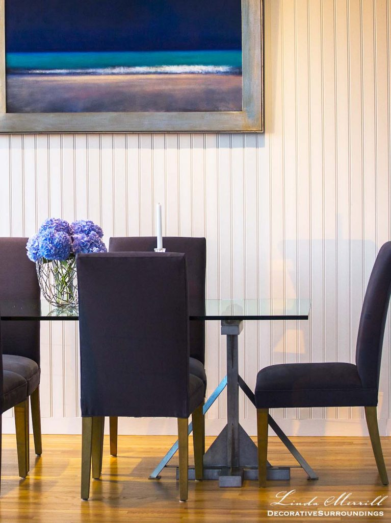 Modern Coastal House dining room in Truro, Massachusetts with blue chairs, modern glass dining table and beadboard wall.
