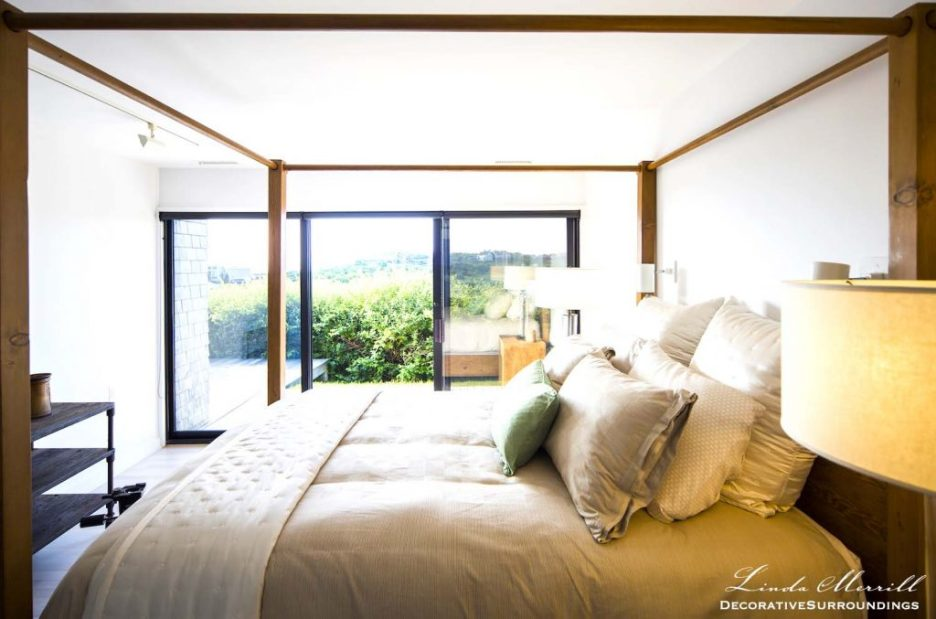 Modern Coastal House bedroom in Truro, Massachusetts with modern canopy bed and beige silk bedding.
