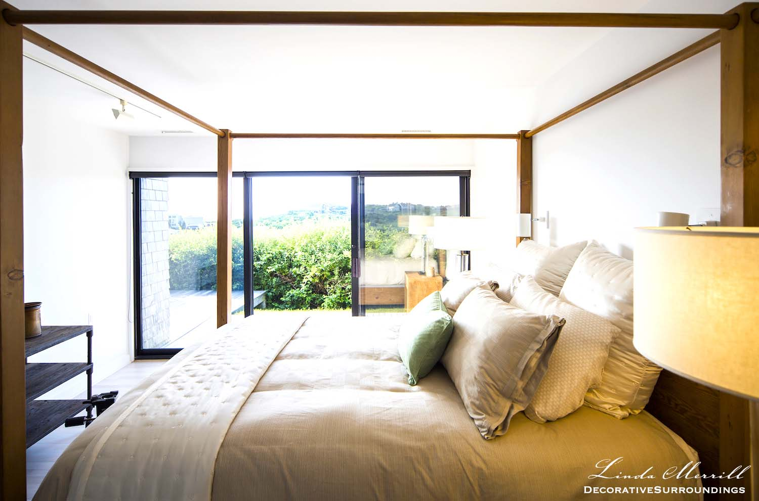 Modern beach house in Truro, MA on Cape Cod bedroom with rustic four poster bed and beige silk bedding