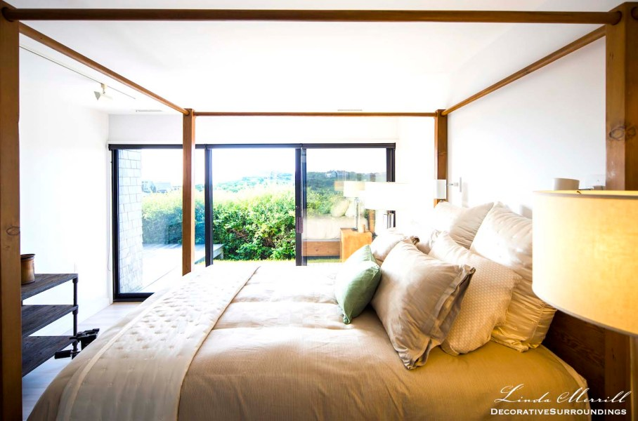 Modern beach house bedroom in Truro, Massachusetts with modern canopy bed and beige silk bedding.
