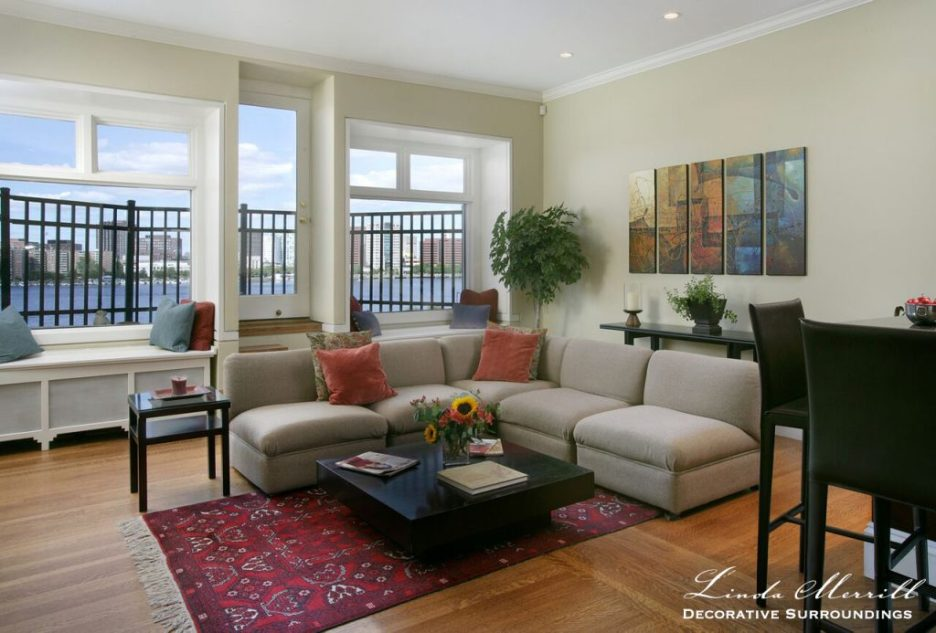 Design by Linda Merrill Decorative Surroundings: Back Bay Bachelor Penthouse with beige sectional red oriental carpet,contemporary art, view of Charles River