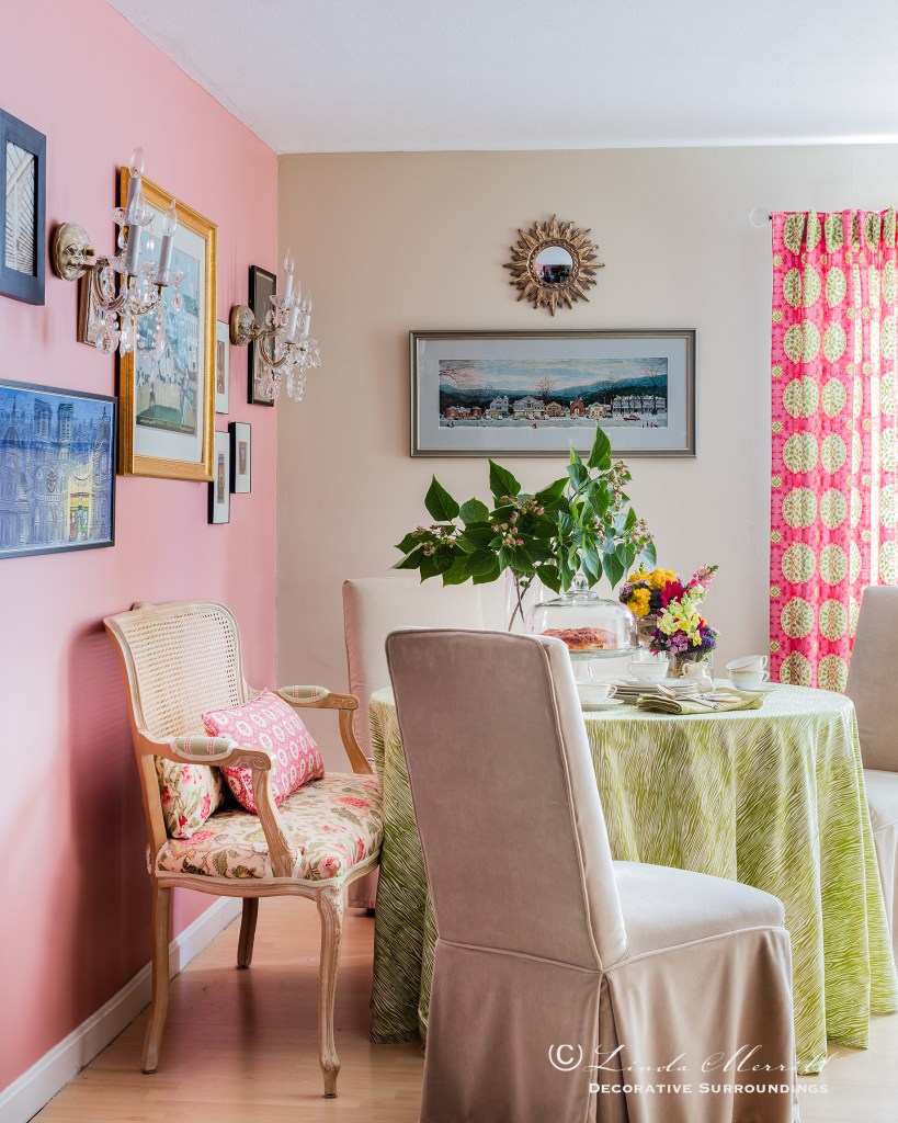 Design by Linda Merrill Decorative Surroundings: Colorful waterfront cottage Dining space with pink accent wall, slipcovered chairs, table skirt, french settee, pink and green colors Massachusetts 02332