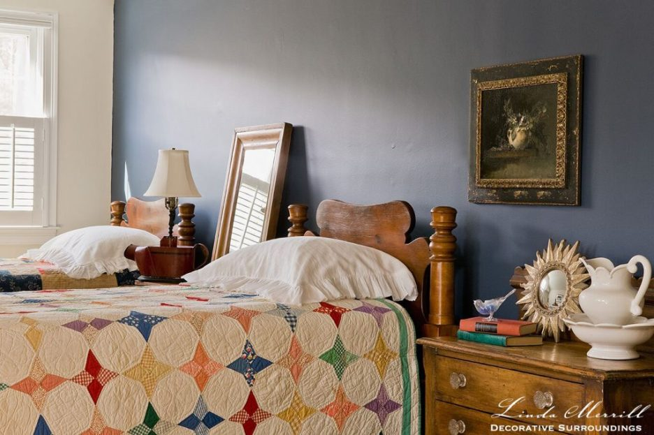 Design by Linda Merrill Decorative Surroundings: Coastal Home bed room in Duxbury MA white dark blue wall, colorful antique quilts antique furniture fine art