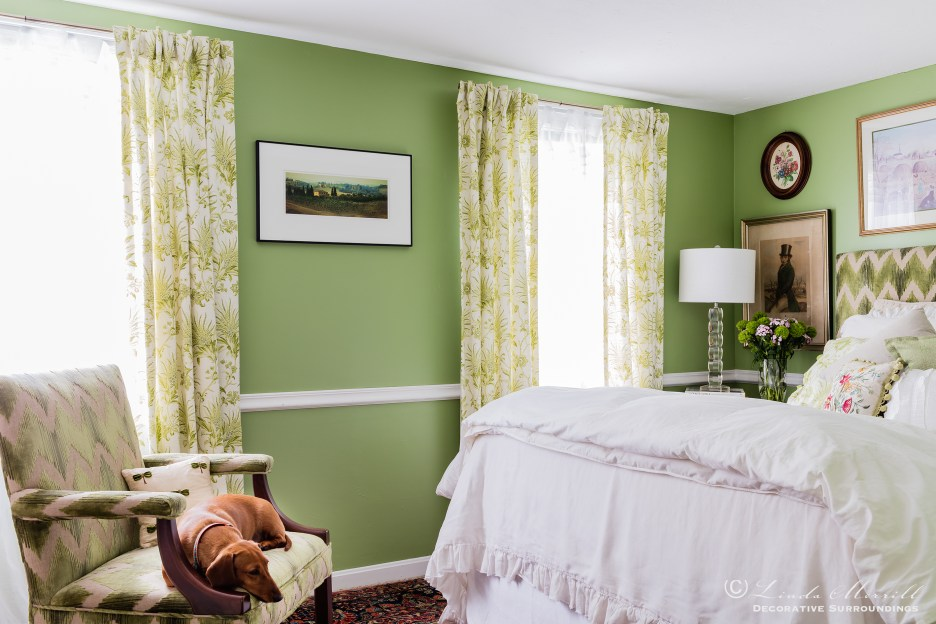 Design by Linda Merrill Decorative Surroundings: Colorful waterfront cottage A green and white bedroom with upholstered chair and matching upholstered headboard, white linen bedding, dachshund  Massachusetts 02332
