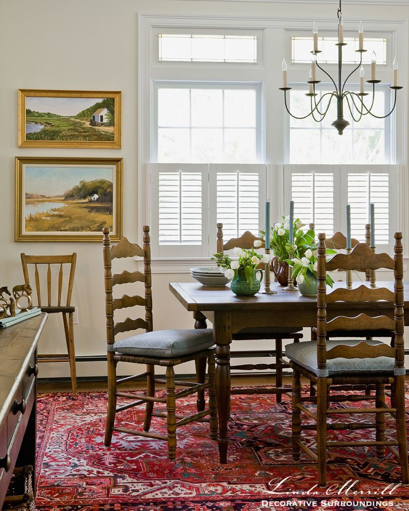 Coastal Home dining room in Duxbury MA ladder back antique chairs with seat cushions antique table wrought iron chandelier fine art red oriental carpet
