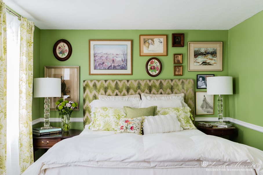 Colorful waterfront cottage A green and white bedroom with upholstered headboard, white linen bedding