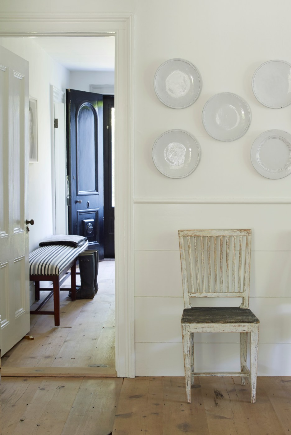 the Hamptons Antique home with wide pine floors, white walls, white plates on wall, white chippy chair, front hall with black door, bench seat