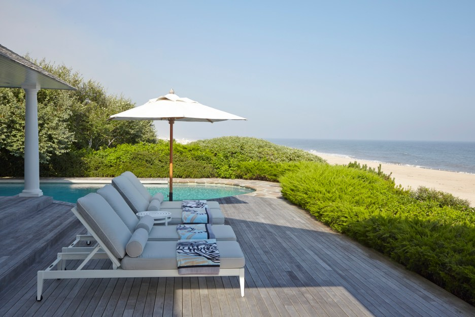 the Hamptons Lounge chairs overlooking Atlantic Ocean on wood deck with pool and beach, umbrella.