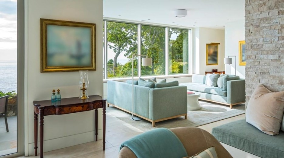 Spectacular oceanside modern beach house in Manchester-By-The-Sea Massachusetts. #modern #beach #coastal #home #oceanside #views #stone #glass #living #room #livingroom #blue #green #sofa #upholstery #beige #gray