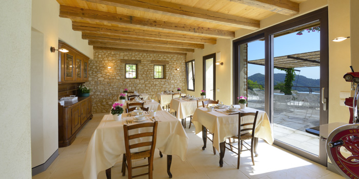 Agritourismo Relais Dolcevista dining room with wood beamed ceiling, white table cloth tables and wood chairs