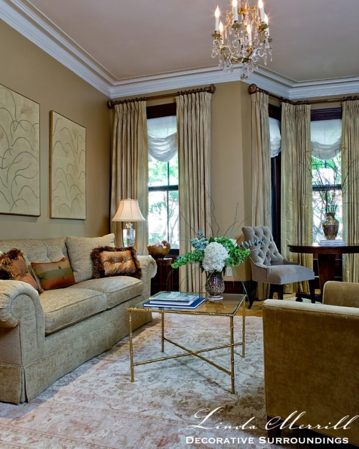 A formal living room with gold and tan color palette, oriental rug, gold sofa, drapery and sheer shades, brass bamboo coffee table