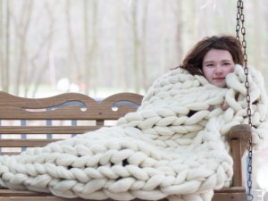 Girl on swing with chunky knit blanket