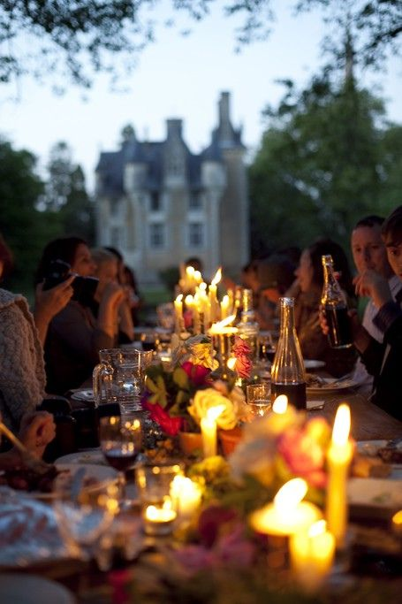 Outdoor dining in front of a castle with candle light