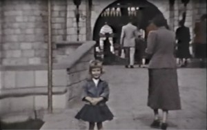B/W photo of little girl standing on the bridge in front of Disneyland's Sleeping Beauty's Castle