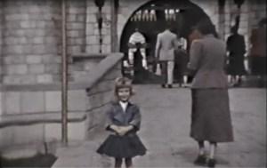 B/W photo of little girl standing on the bridge in front of Disneyland's Sleeping Beauty's Castle