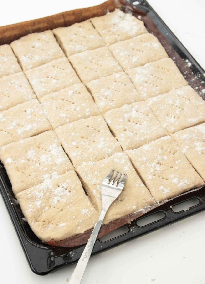 2. Tryck eller kavla ut 2/3 av degen på en ugnsplåt med bakplåtspapper. Skär degen i ett rutmönster, 5 x 4. Nagga degen med en gaffel.