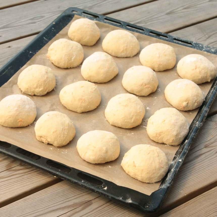 3. Rulla ca 16 runda bullar av degen och lägg dem på en plåt med bakplåtspapper. Låt dem jäsa under bakduk i ca 30 min. Sätt ugnen på 250 grader.