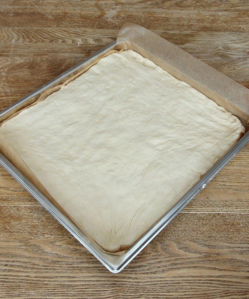3. Tryck ut degen med mjölade händer i en långpanna, ca 29 x 32 cm, klädd med bakplåtspapper. Låt degen jäsa under bakduk i ca 30 min. Sätt ugnen på 200 grader.