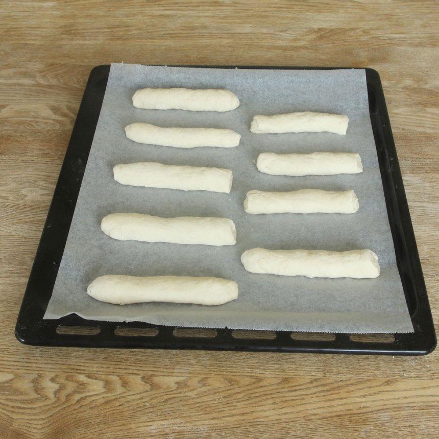 Rulla ut dem till längder, ca 12 cm. Lägg dem brett isär på en plåt med bakplåtspapper. Låt dem jäsa under bakduk i ca 30 min. Sätt ugnen på 250 grader.