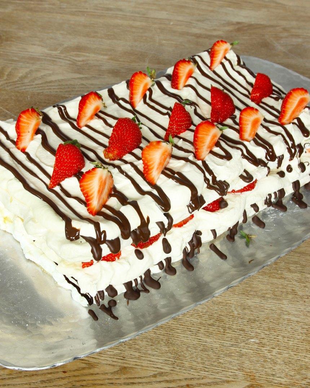 6. Lägg på den andra bottnen ovanpå grädden och jordgubbarna. Ringla smält choklad över den översta marängbottnen. Låt den stelna. Bred ut grädde. Ringla choklad över grädden och garnera med jordgubbar. Förvara tårtan i kylen!