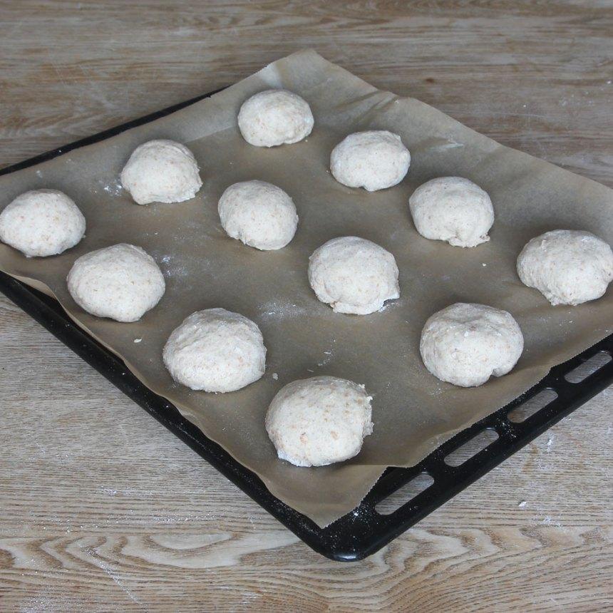 3. Rulla bollar av degen och lägg dem på en plåt med bakplåtspapper. Låt dem jäsa under bakduk i ca 30 min. Sätt ugnen på 250 grader.