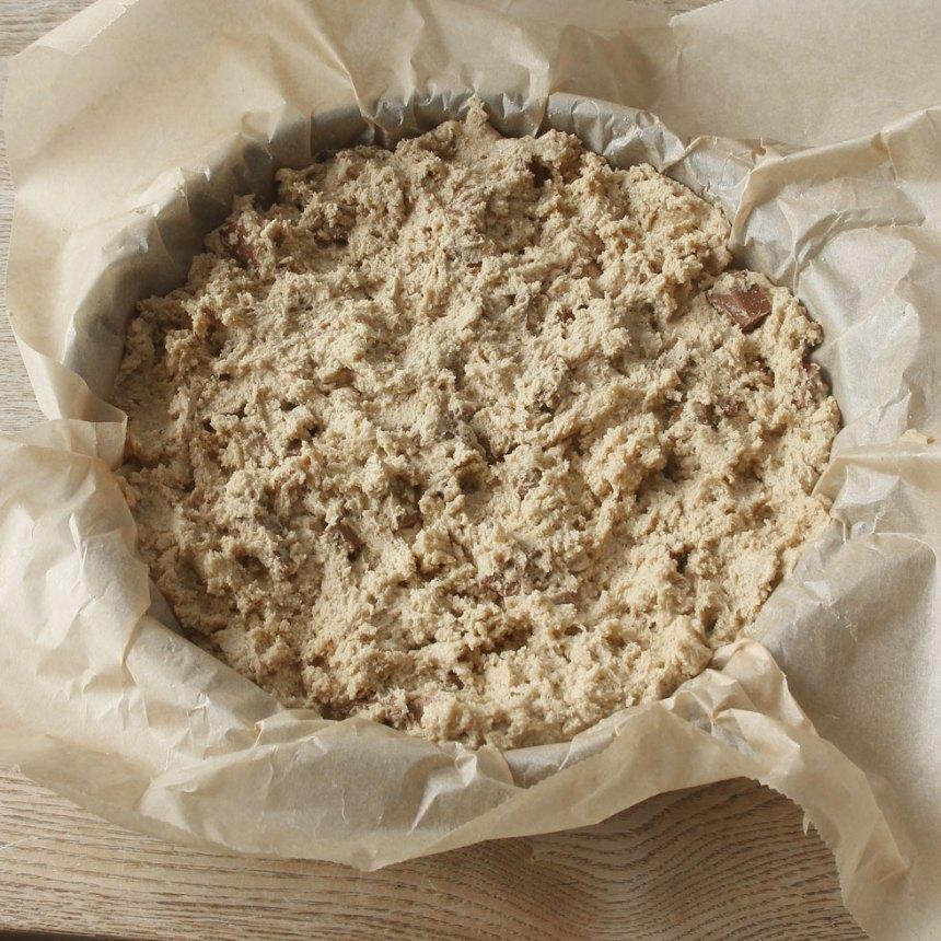4. Smula ner degen i en smord och bröad springform, 22–23 cm i diameter. Strö över resten av den grovhackade chokladen.