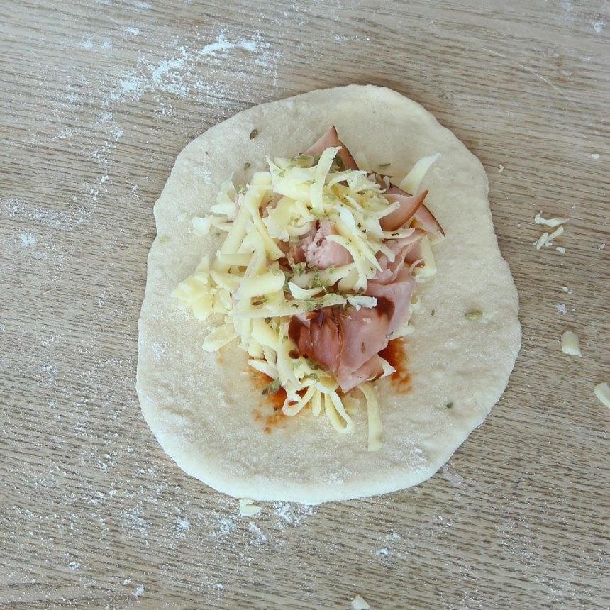 4. Lägg 1–2 msk riven ost samt ungefär lika mycket skivad skinka i en liten hög mitt på degbitarna.