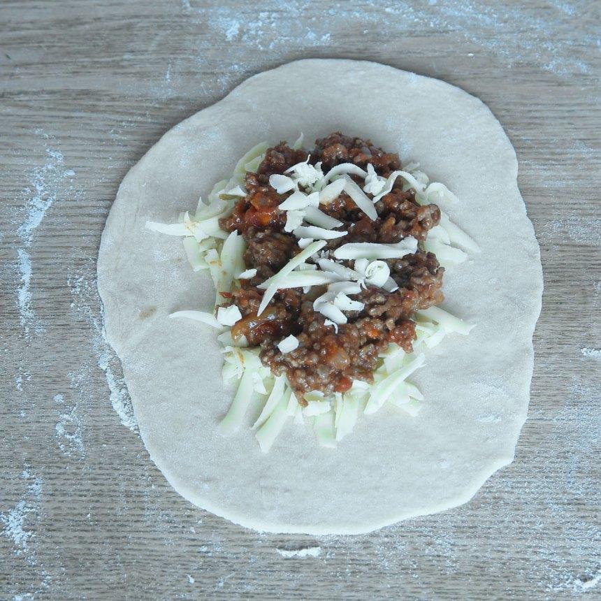 3. Bred ut riven ost och ungefär lika mycket köttfärs mitt på degbitarna.