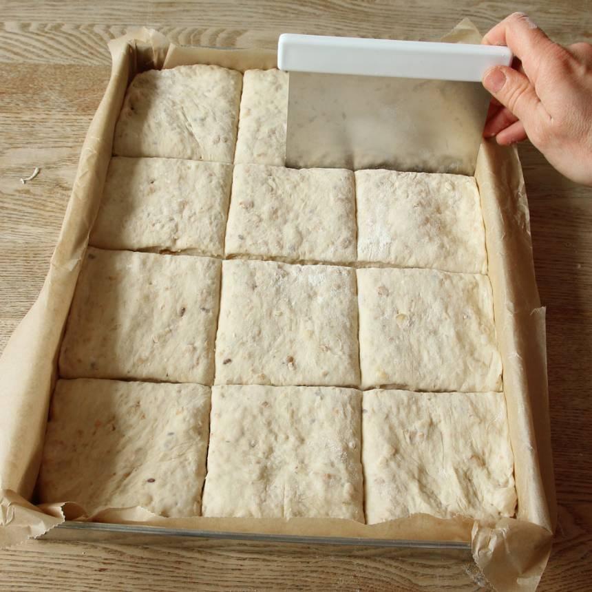 3. Skär degen i rutor, ca 12 st med en degskrapa eller kniv. Låt det jäsa under bakduk i ca 30 min. Sätt ugnen på 250 grader.